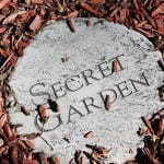 A circular grey concrete slab with the words secret garden etched onto the slab. It is on the ground with wood chipping and bark all around it.